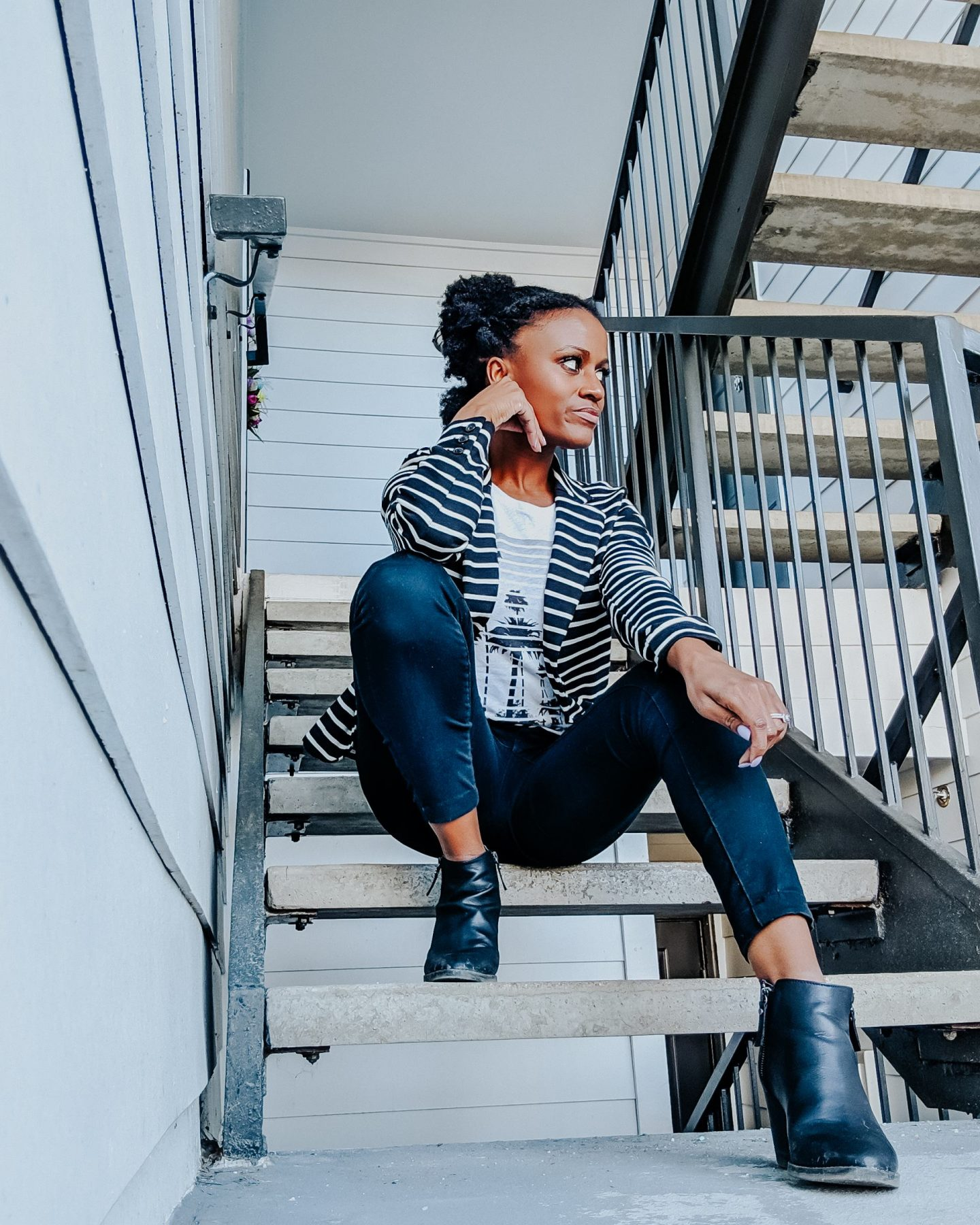 Black woman sitting on stairs with black and white striped blazer and shirt, black pants, black booties, hand on chin looking to the right.